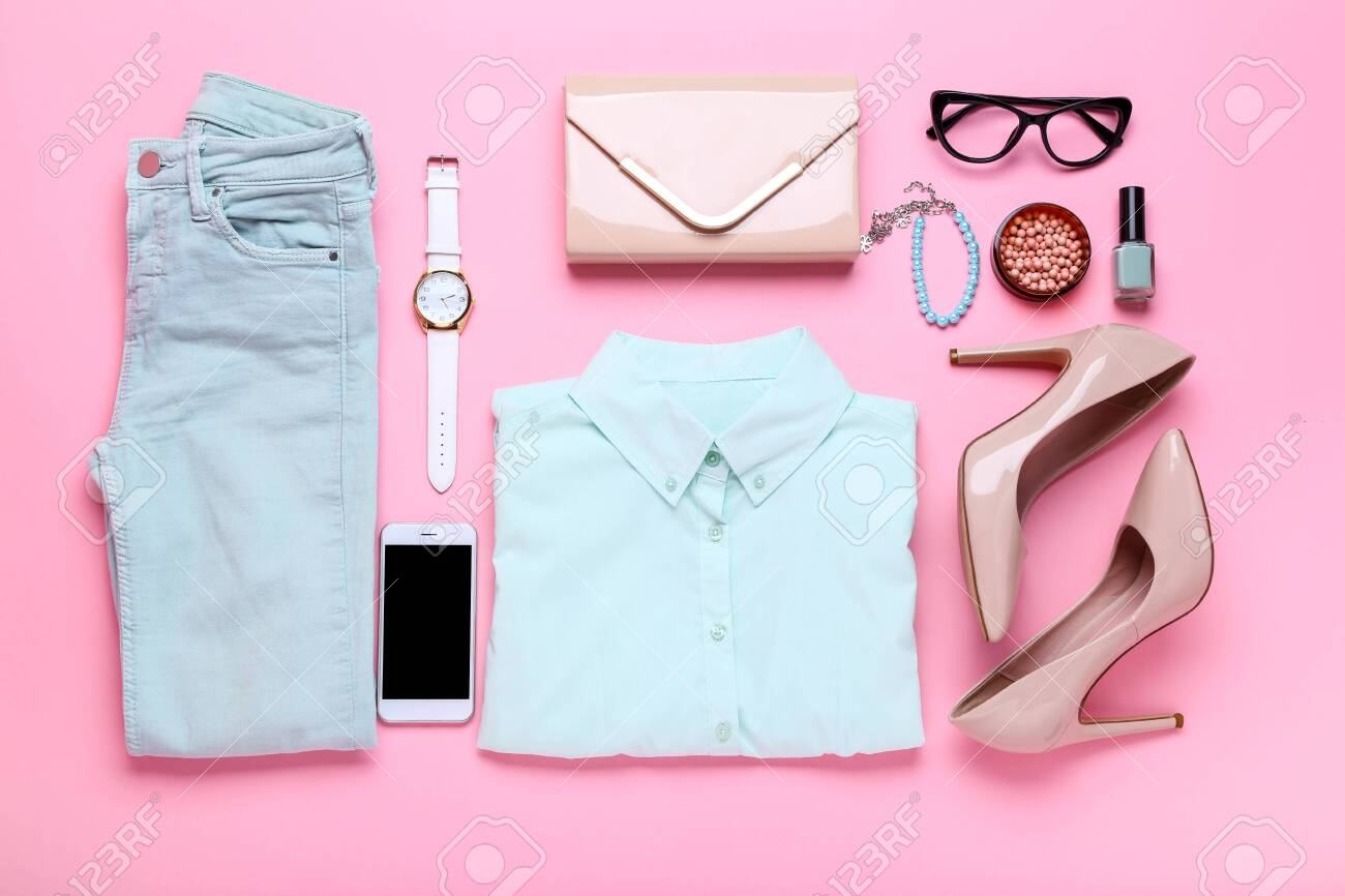 Stylish women's clothes with accessories and cosmetics on pink background