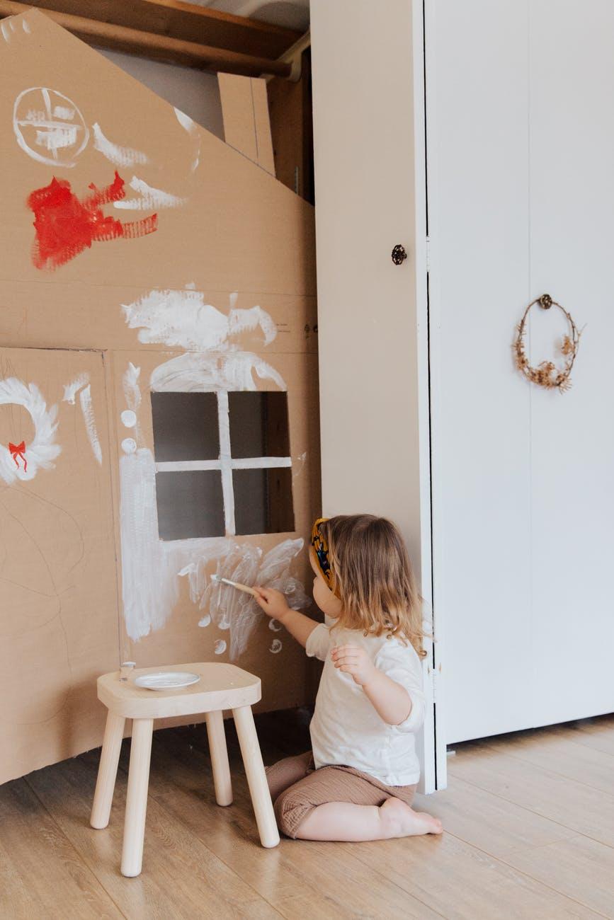 girl painting cardboard house